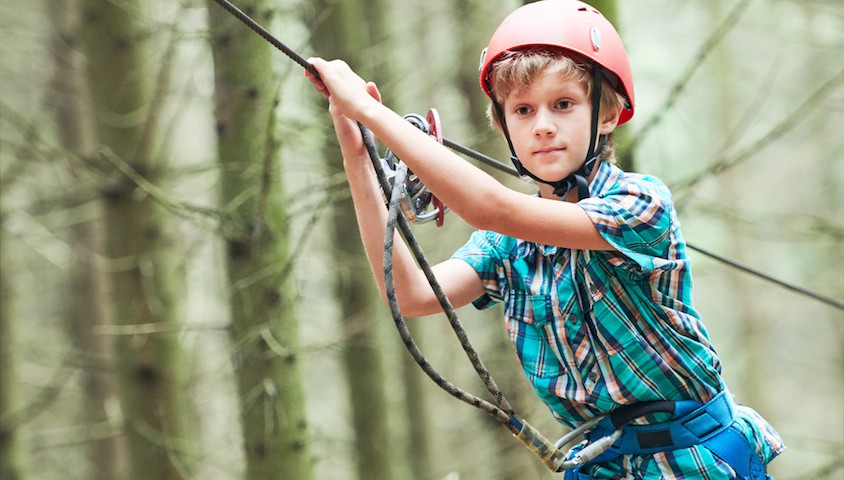 Boy on high ropes course.